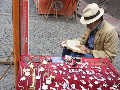 A streetside vendor reads as shoppers jostle past at the San Telmo Sunday Market