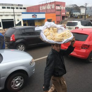 A street vendor weaves in between cars, deftly balancing a large basket of chipás
