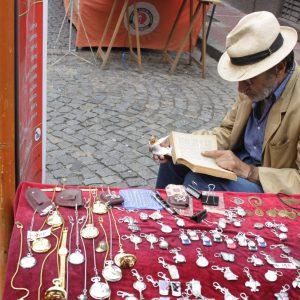 A streetside vendor reads as shoppers jostle past at the San Telmo Sunday Market