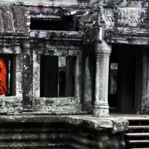 A saffron robed monk disappears into the bowels of Angkor Wat