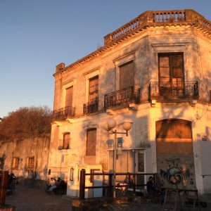 The setting sun casts an orange glow over crumbling buildings